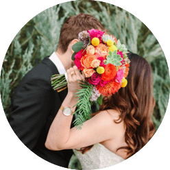 photo of a couple leaning in to kiss while holding a brightly-colored bouquet in front of their faces