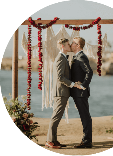 photo of a couple kissing under a wood frame decorated with garlands