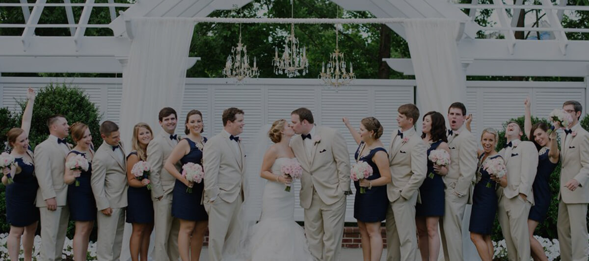 Photo of a couple surrounded by a large wedding party in front of a white outdoor open-barn backdrop, with khaki suits, navy dresses, and pink flower details.