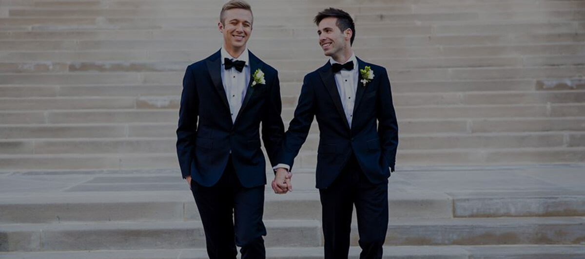 Photo of a couple in matching navy suits and bow-ties, with crisp white and green flower accents, holding hands while walking down light-colored stone steps.